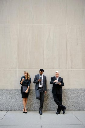 Three businesspeople leaning on a wall, looking at phones and digital tablets
