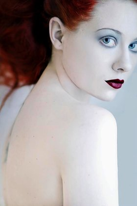 Young female with red hair and bare shoulders looking at camera