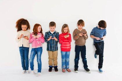 Children using smartphones, standing in a row