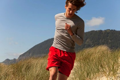 A fit young man runs on a beach trail in sand dunes.