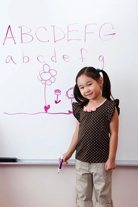 Girl in front of whiteboard with alphabet