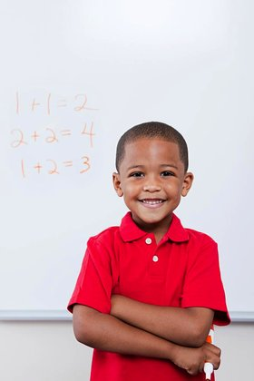 Happy schoolboy in front of mathematics on whiteboard