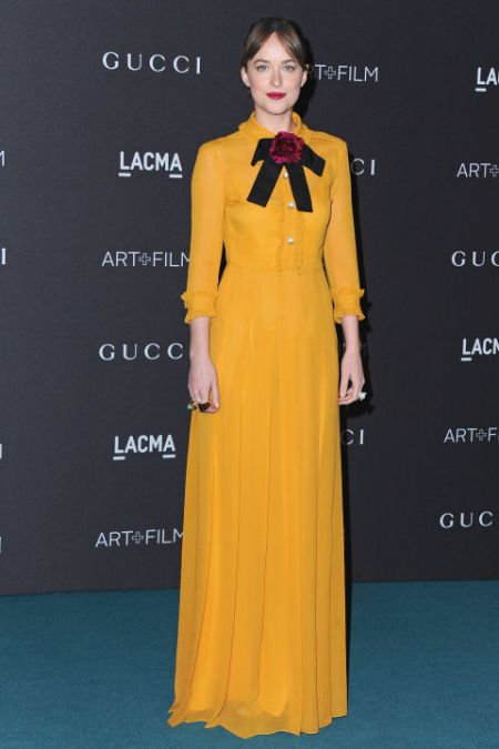 Dakota Johnson getting her Pilgrim on in a squash colored frock